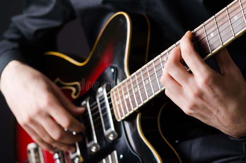 Mens met gitaar tijdens overleg royalty-vrije stock fotografie