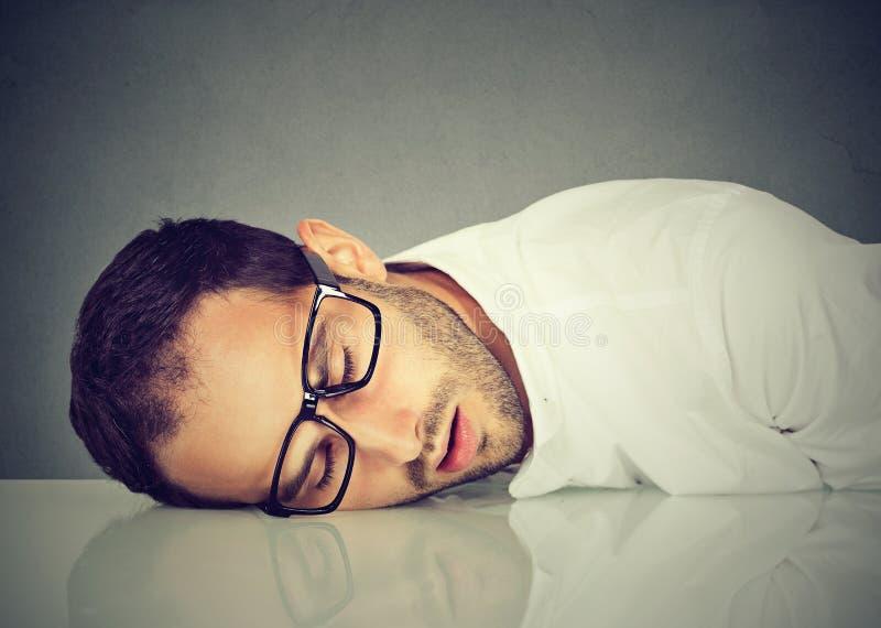 Mens met glazen die op bureau slapen stock afbeeldingen