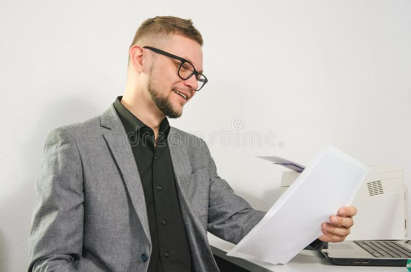 Mens met glazen en jasjeglimlachen die documenten bestuderen royalty-vrije stock afbeeldingen