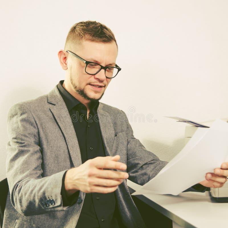 Mens met glazen en jasjeglimlachen die documenten bestuderen stock foto's
