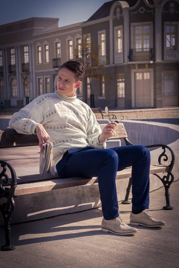 Mens met glazen in witte sweater die op bank situeren en Ne houden stock afbeelding