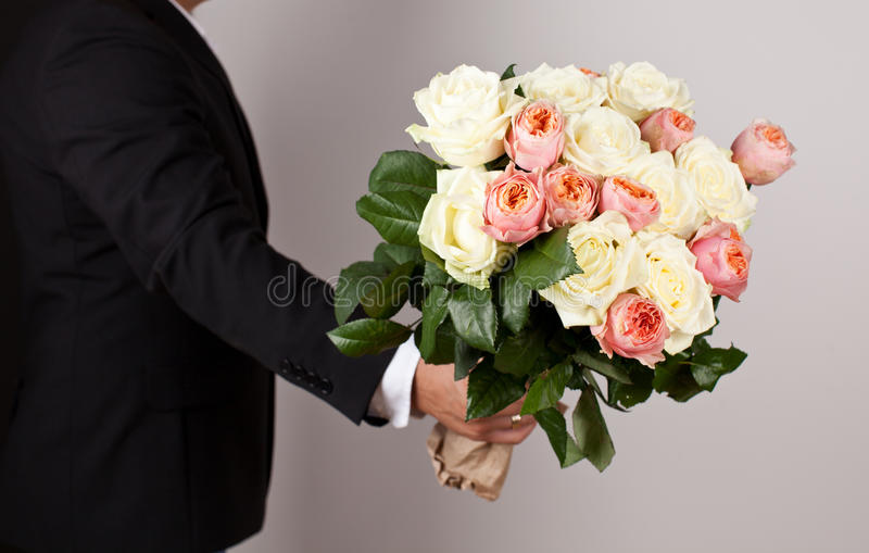 Mens met groot mooi boeket van aardige bloemen stock afbeelding