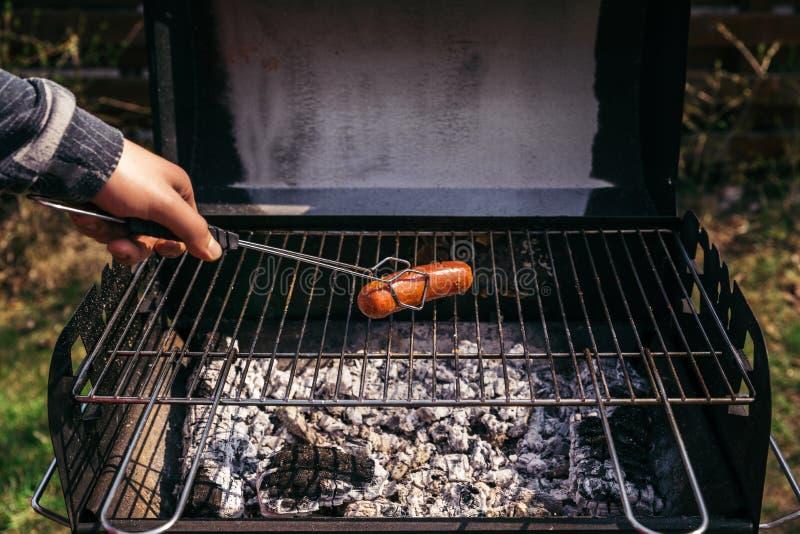 Mens met het dienen van tang die worsten in openlucht bij de grill koken stock fotografie