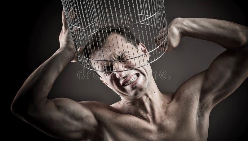 Mens met het hoofd binnen een birdcage royalty-vrije stock afbeelding