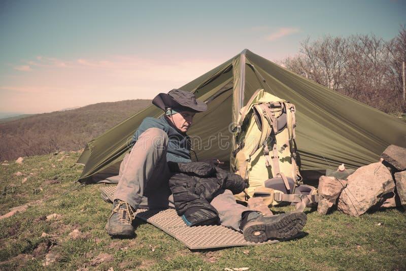 Mens met Hoed die dichtbij Zijn Tent rusten stock foto