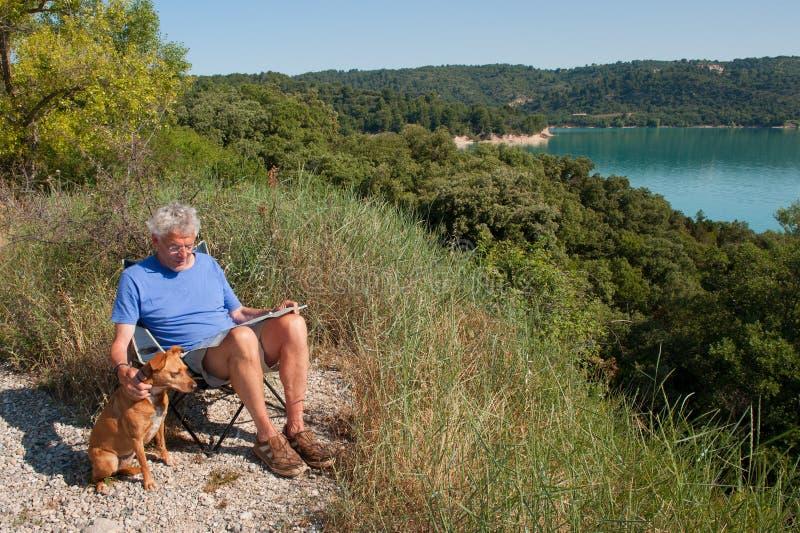 Mens met hondzitting in Frans landschap royalty-vrije stock foto