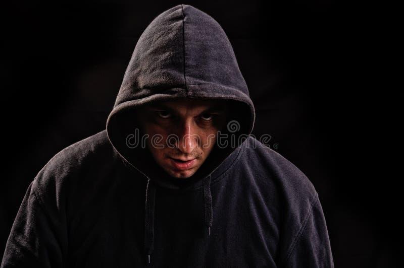 Mens met hoodie of hooligan over donkere achtergrond stock afbeelding