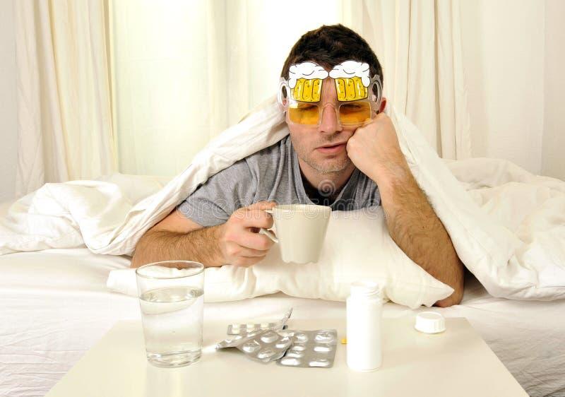 Mens met hoofdpijn en kater in bed met tabletten stock foto