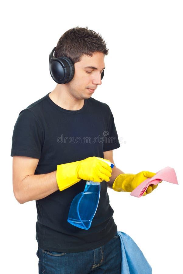 Mens met hoofdtelefoons die huis schoonmaken stock fotografie