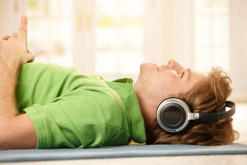 Mens met hoofdtelefoons op vloer royalty-vrije stock afbeeldingen