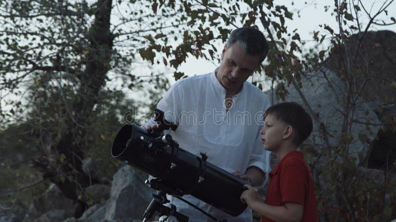 Mens met jongen die telescoop gebruiken royalty-vrije stock afbeelding