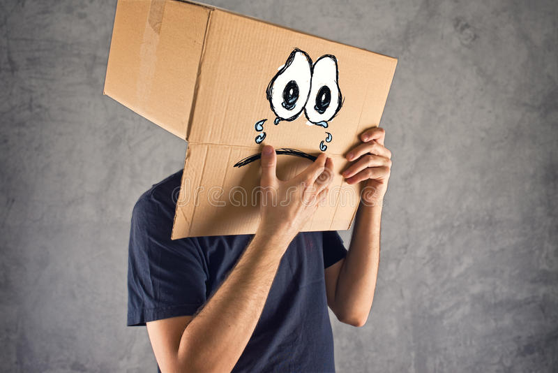 Mens met kartondoos op zijn hoofd en droevige gezichtsuitdrukking royalty-vrije stock afbeeldingen