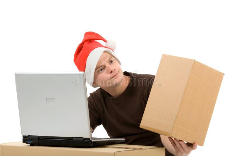 Mens met Kerstmishoed en laptop stock afbeeldingen