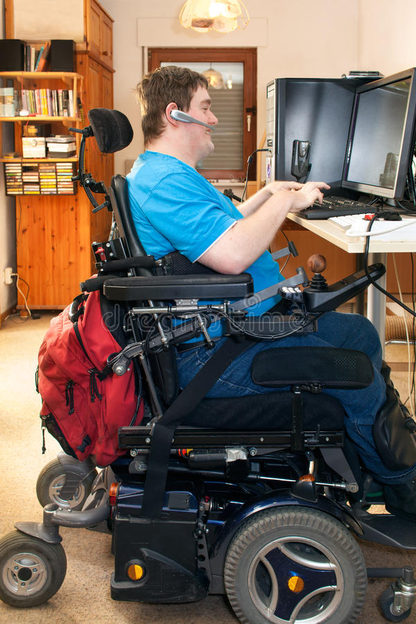 Mens met kinder hersenverlamming die een computer met behulp van stock fotografie