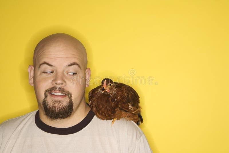 Mens met kip op zijn schouder. stock afbeelding