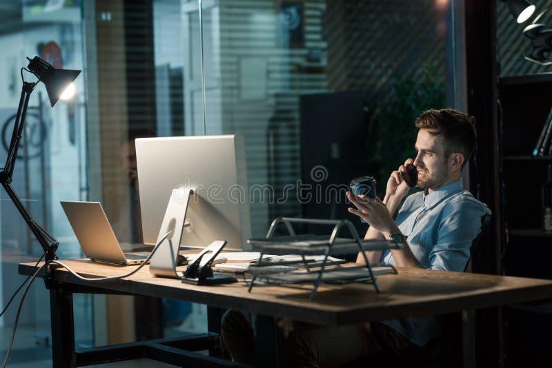 Mens met koffie het spreken telefoon laat in bureau stock afbeeldingen