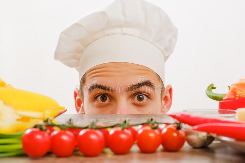 Mens met kok GLB op witte achtergrond Chef-kok met groenten op lijst Kok met vrolijk gezicht in gezichts dichte omhooggaand stock foto