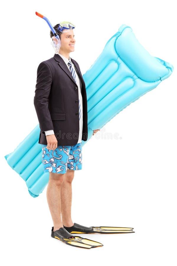 Mens met kostuum dragende zwemmende matras stock foto's