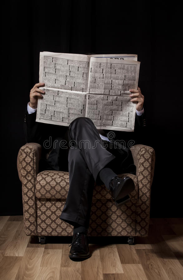 Mens met krantenzitting in uitstekende leunstoel stock afbeeldingen