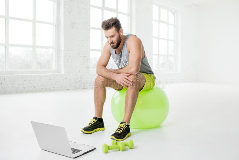 Mens met laptop in de gymnastiek stock foto