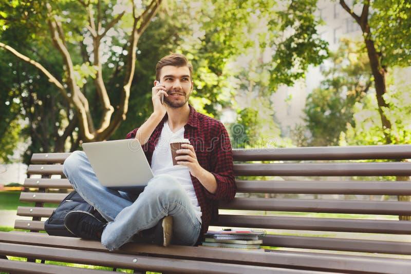 Mens met laptop, die op smartphone in openlucht spreken stock foto