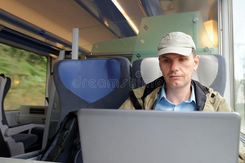 Mens met laptop in een trein royalty-vrije stock afbeeldingen