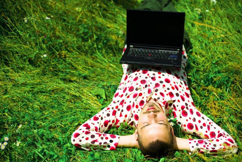 Mens met laptop op gras royalty-vrije stock fotografie