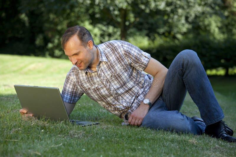Mens met laptop op het gras royalty-vrije stock fotografie