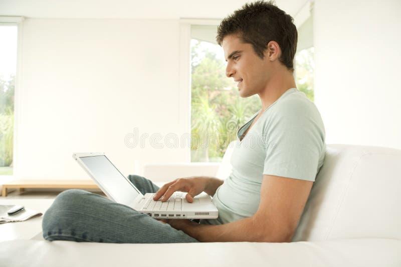 Mens met Laptop thuis stock afbeelding
