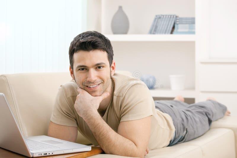 Mens met laptop thuis stock fotografie