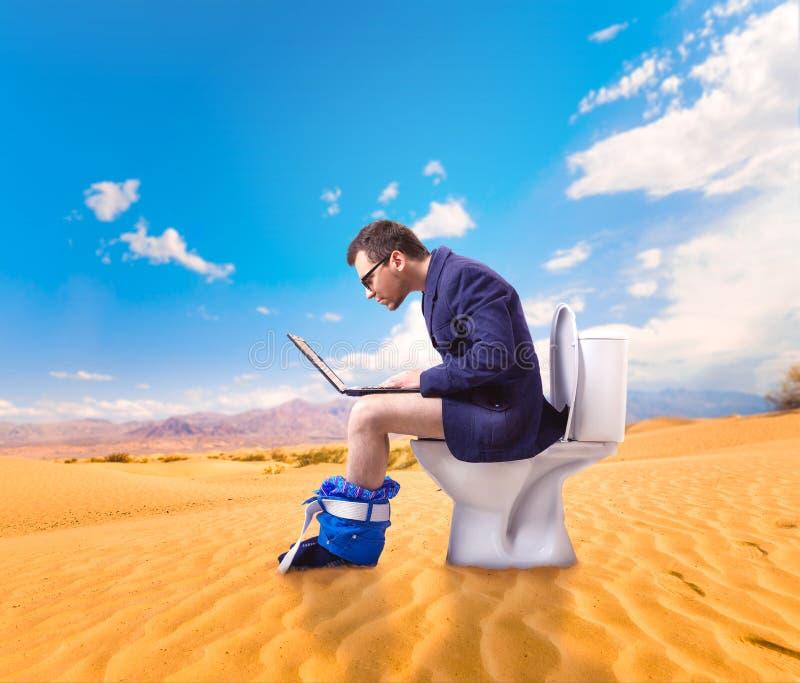 Mens met laptop zitting op toiletkom in woestijn stock foto
