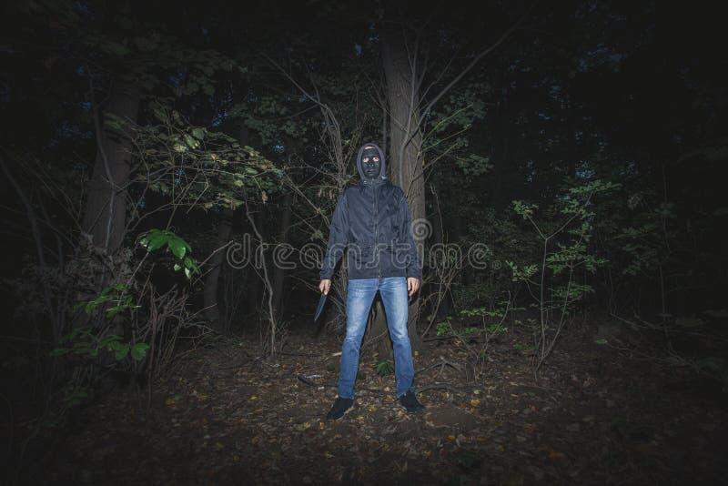 Mens met masker en mes in het hout royalty-vrije stock afbeelding