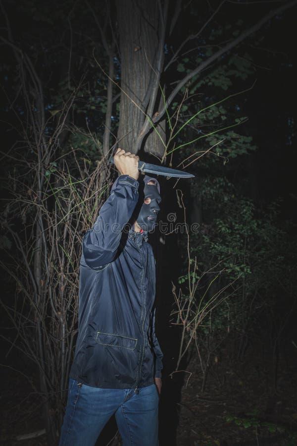 Mens met masker en mes in het hout stock afbeeldingen