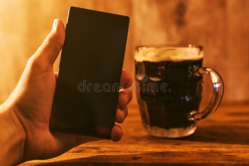 Mens met mobiele en donkere biermok royalty-vrije stock fotografie
