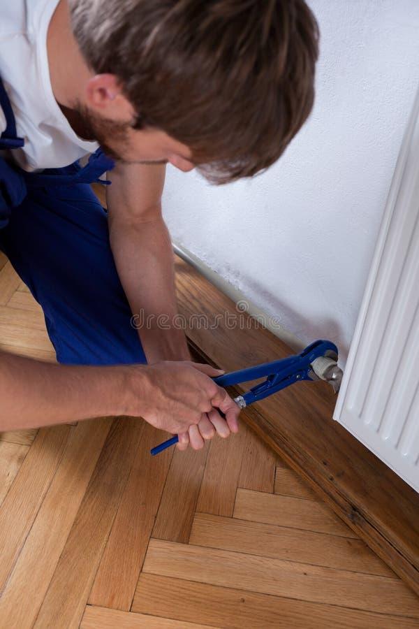 Mens met moersleutel het bevestigen radiator royalty-vrije stock fotografie