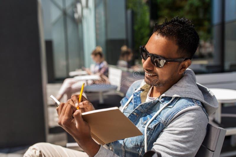 Mens met notitieboekje en koffie bij straatkoffie stock afbeeldingen