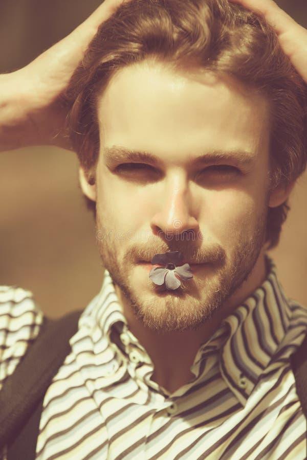Mens met ongeschoren gezicht die blauwe bloem in mond houden royalty-vrije stock fotografie