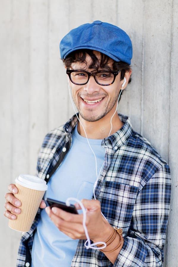 Mens met oortelefoons en smartphone het drinken koffie royalty-vrije stock fotografie