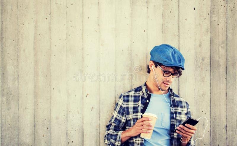 Mens met oortelefoons en smartphone het drinken koffie stock foto's