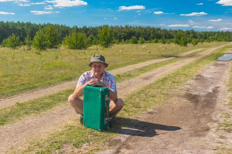 Mens met oude kofferzitting op een landweg terwijl het hebben van korte rust in de reis stock afbeeldingen