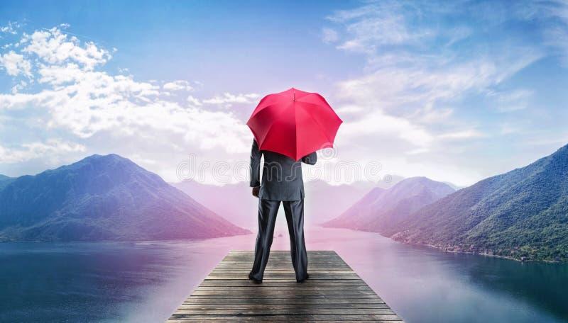 Mens met paraplu die zich op tepijler bevinden royalty-vrije stock afbeeldingen