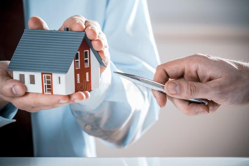 Mens met Pen Pointing Miniature House van een Agent royalty-vrije stock afbeelding