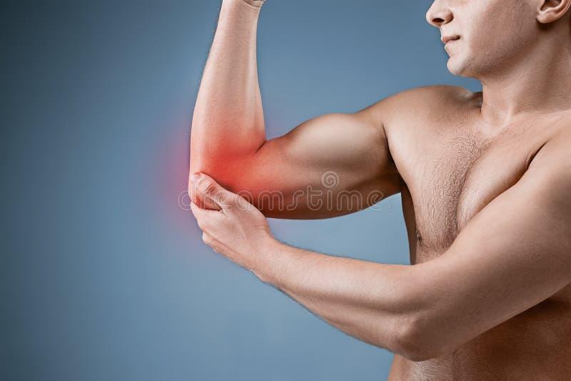 Mens met Pijn in Elleboog Het concept van de pijnhulp stock afbeeldingen