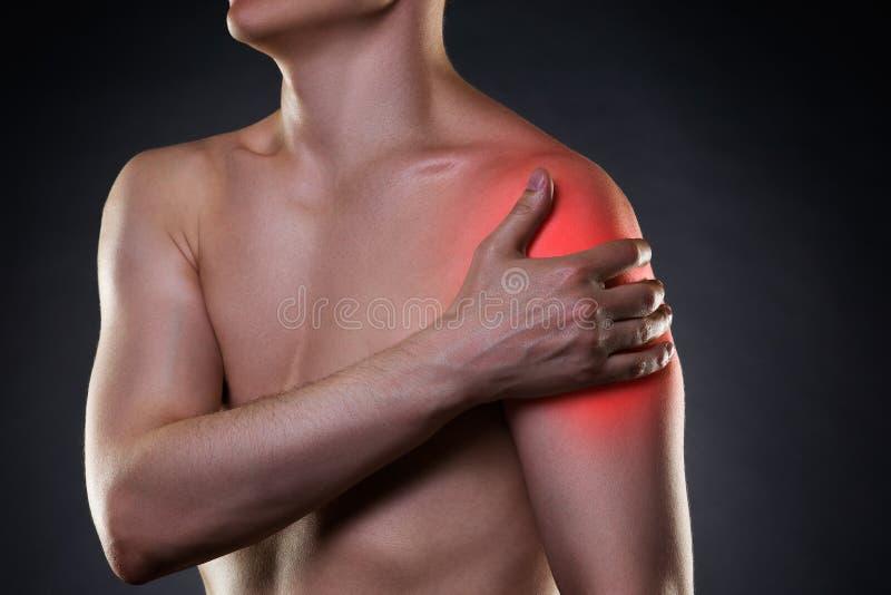 Mens met pijn in schouder op zwarte achtergrond stock afbeelding