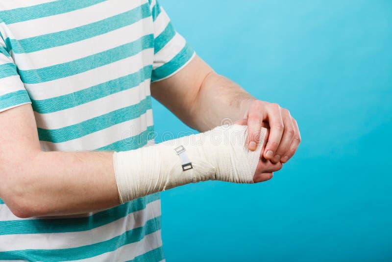 Mens met pijnlijke verbonden hand stock afbeelding