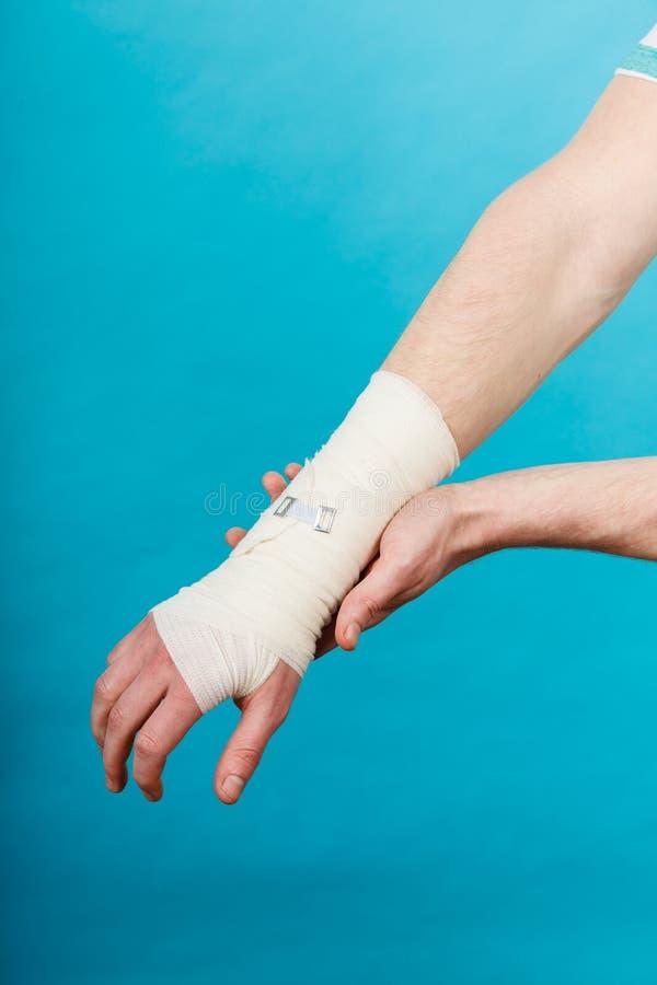 Mens met pijnlijke verbonden hand stock foto's
