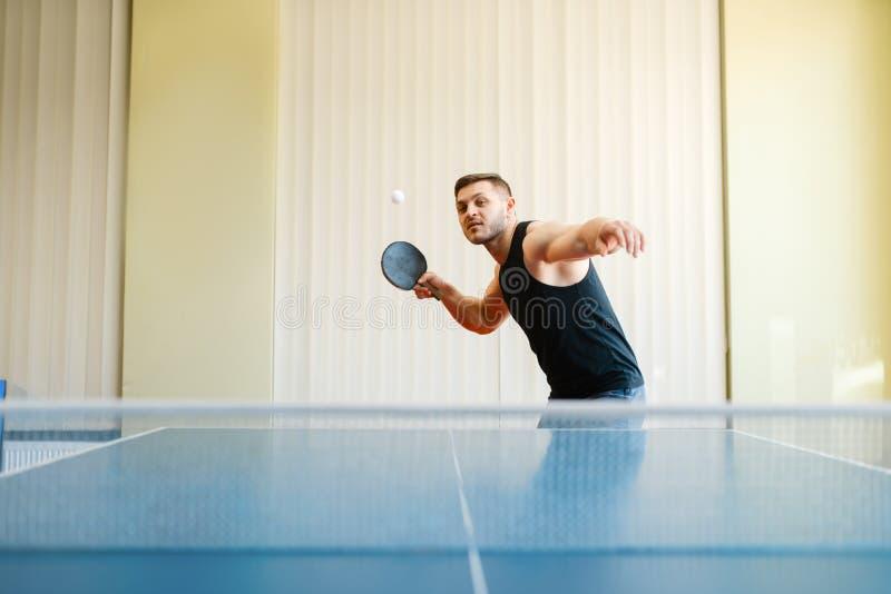 Mens met racket en bal speelpingpong binnen stock foto's