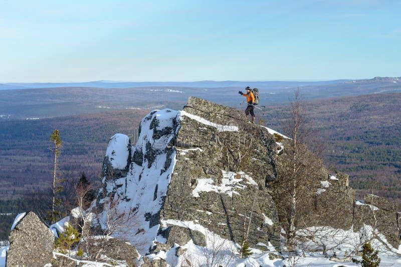 Mens met rugzaktrekking in bergen bij de winter Wandelaar die die aan de rots beklimmen met sneeuw wordt behandeld royalty-vrije stock foto