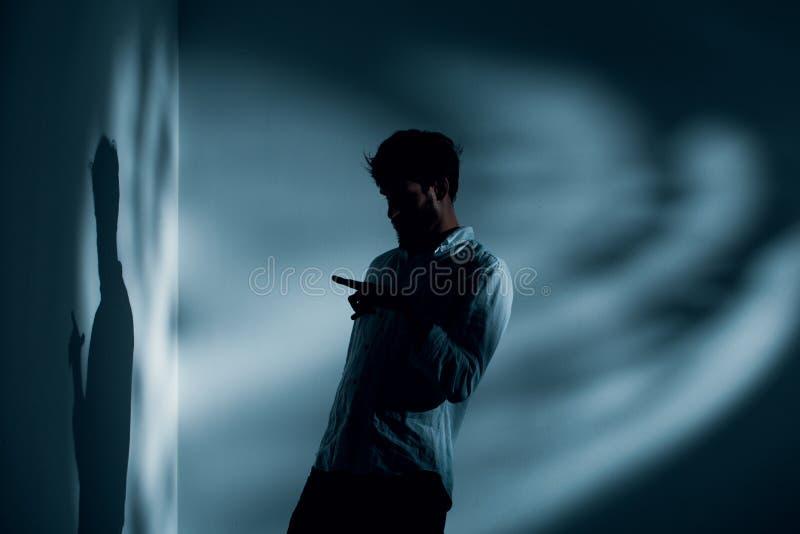 Mens met schizofrenie die zich alleen in het donkere binnenlandse spreken aan zijn schaduw bevinden, foto met exemplaarruimte stock afbeelding