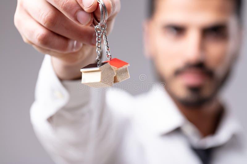 Mens met sleutelringen in vorm van huis stock fotografie